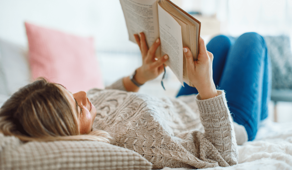 Young woman reading a book on her bed, illustrating data literacy in the digital workplace