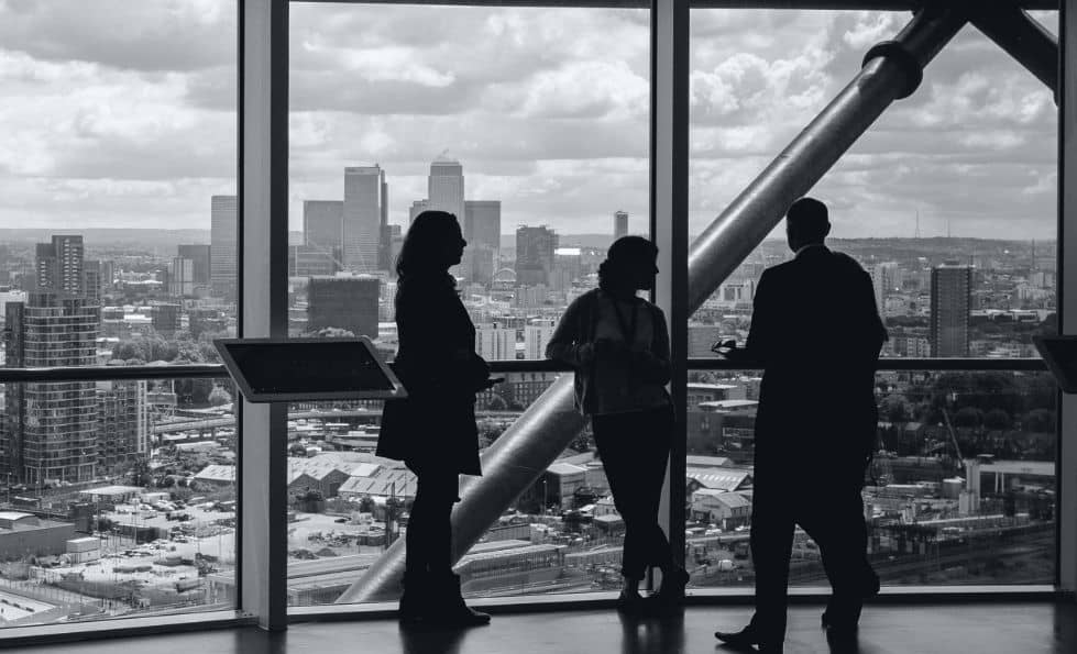 Three people talking at the window looking out over London from a skyscraper