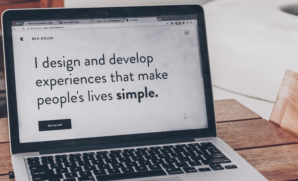 A laptop displaying the message 'I design and develop experiences that make people's lives simple.'
