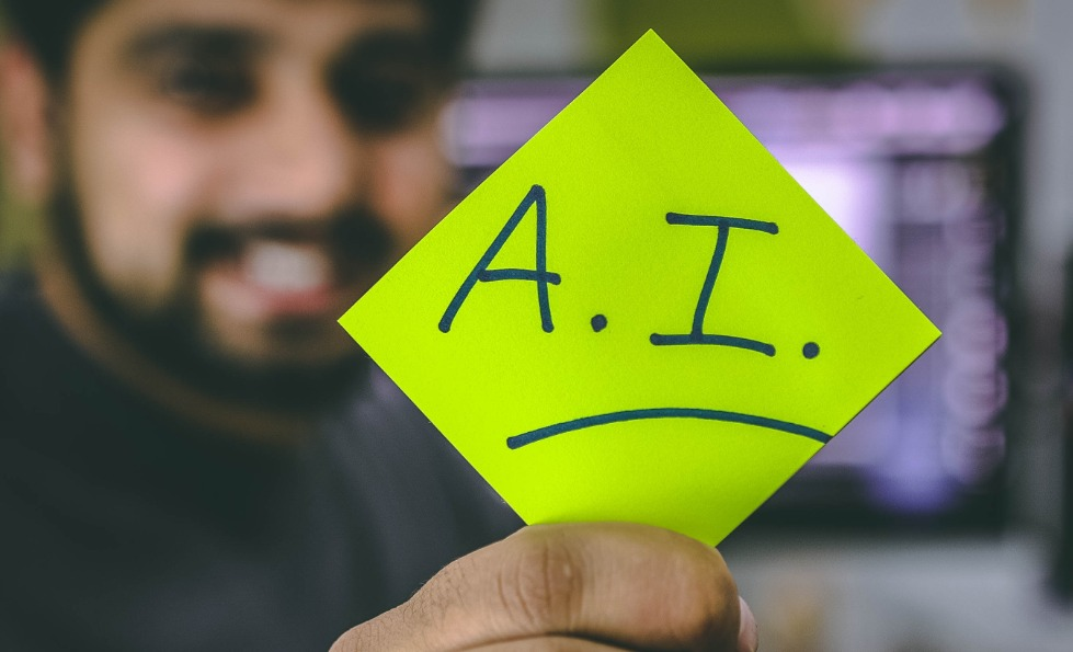 A man holding up a green post-it note with A.I written on it, underlined.