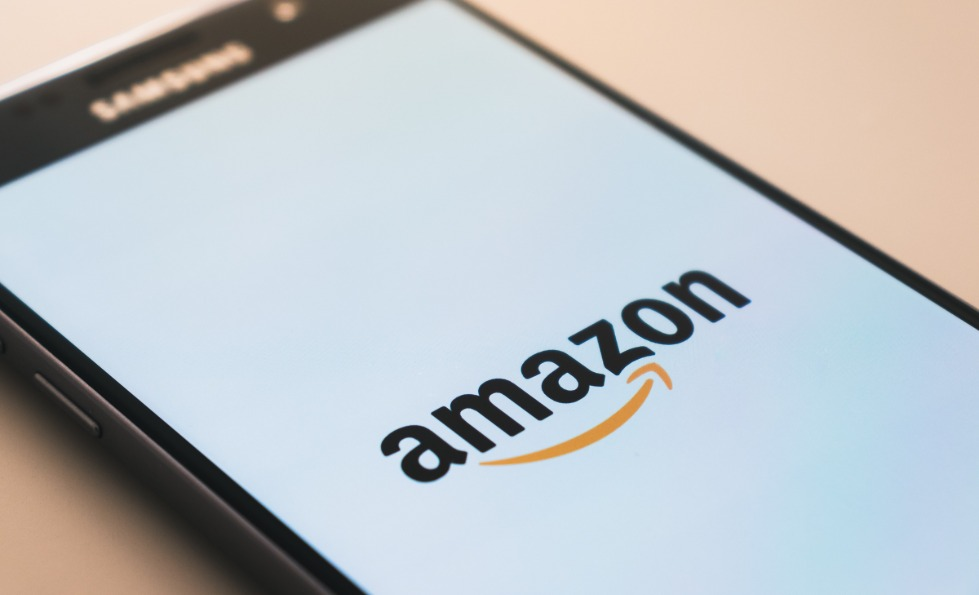 A mobile phone displaying the black and orange Amazon logo on a white screen.