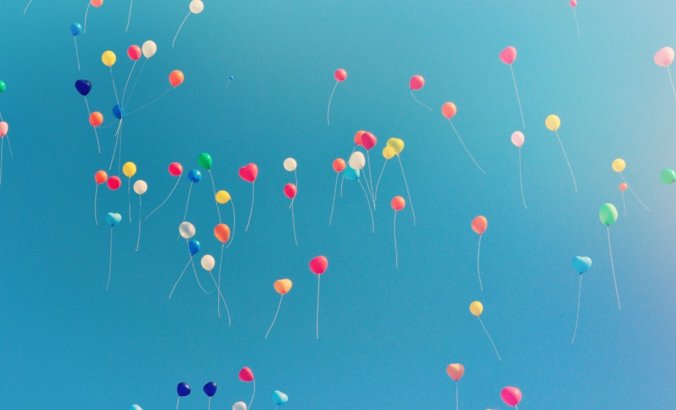 Balloons floating in a blue sky.