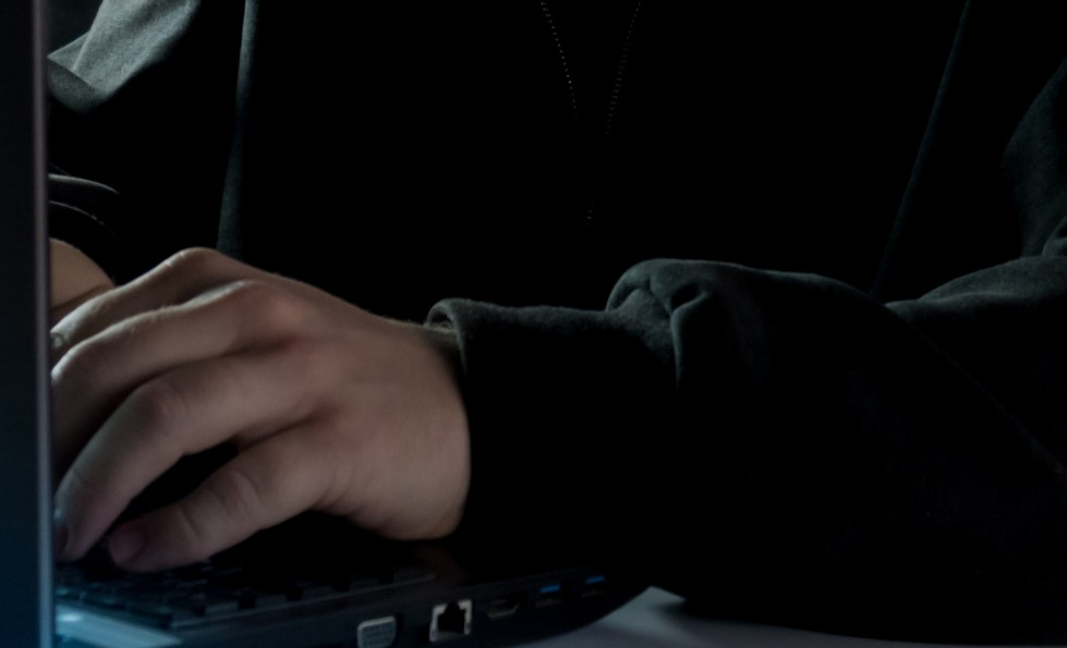 A man in a dark hoodie working on a laptop