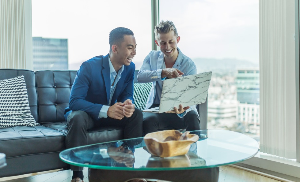 two men laughing about what's on a laptop screen in an office above the city with glass walls.