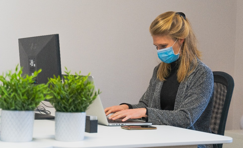 A woman working on a laptop at a desk with a blue face covering on.