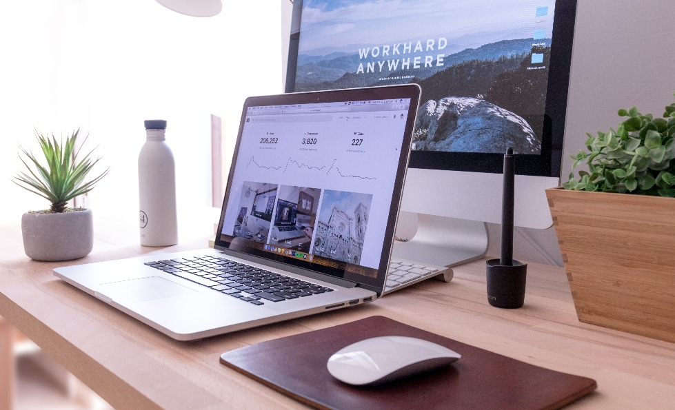 A home office with a laptop, monitor and white mouse positioned on a light coloured wooden desk